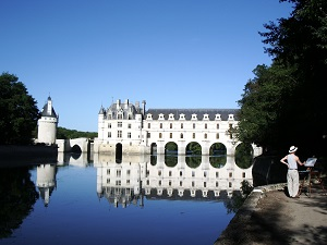 chateau of Chenonceau in summer with painter and Cher river, tributary of the Loire